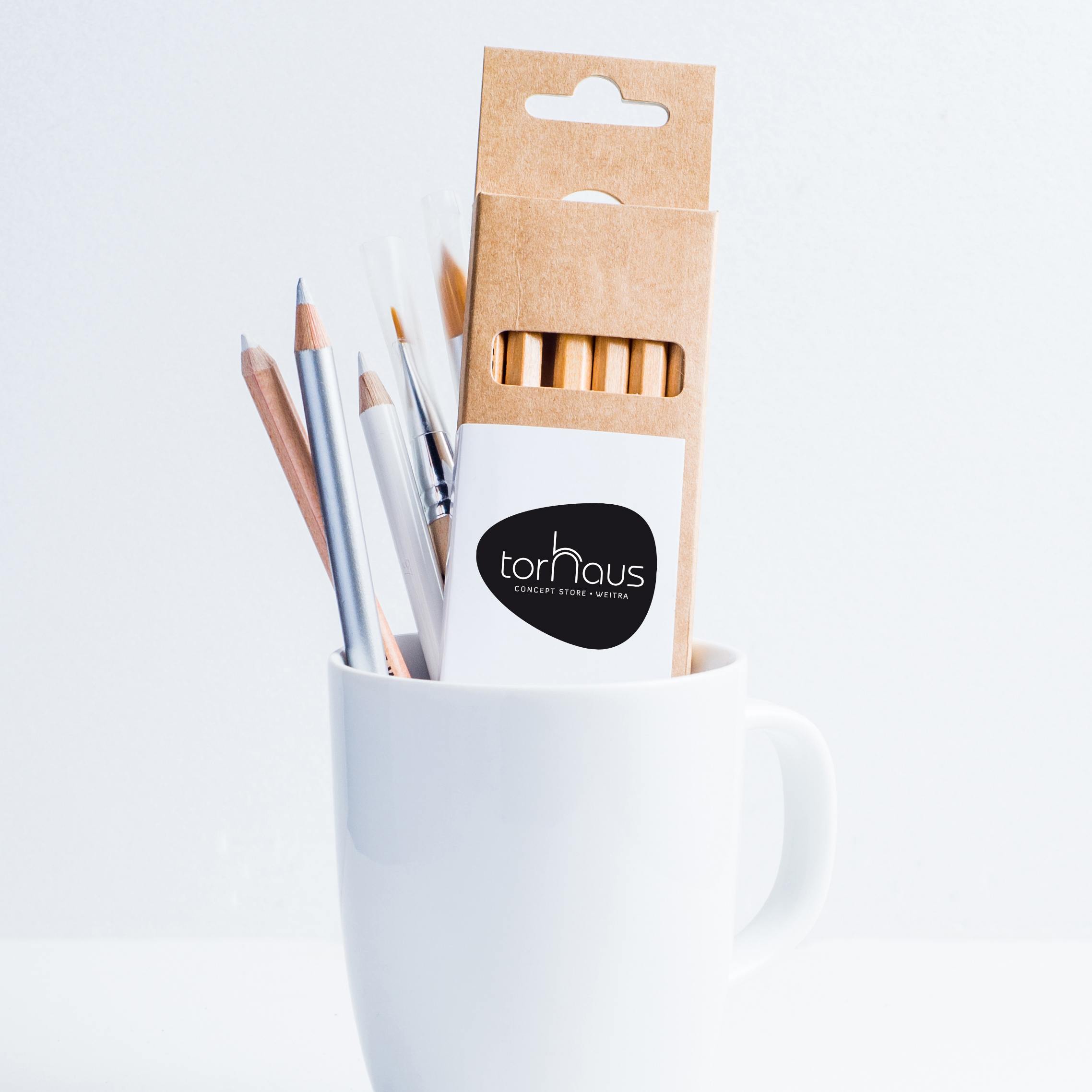 White mug with pencils on white background